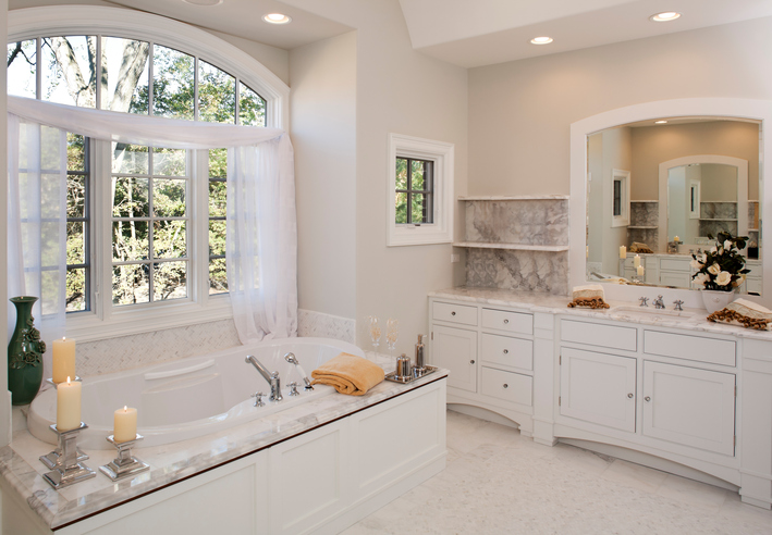Custom white toned master bathroom with jacuzzi tub.