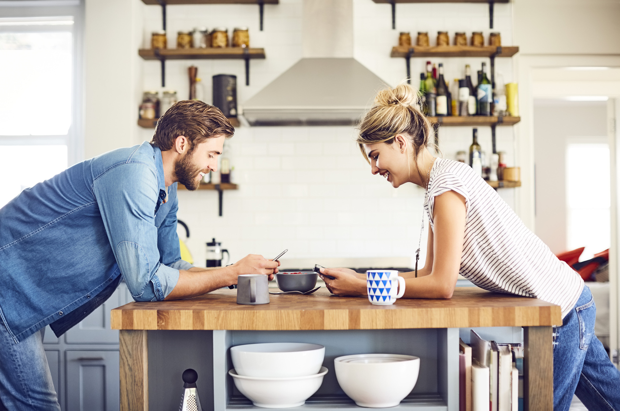 Smiling couple with digital tablets leaning on kitchen island
